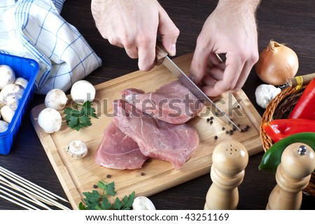 Person slicing pork meat on wooden board - stock photo