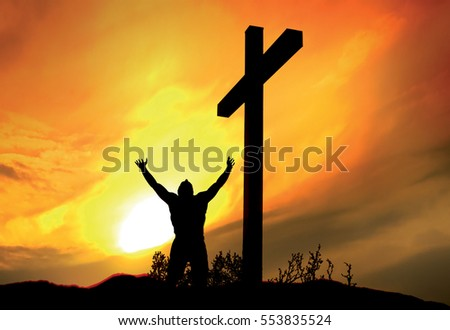 Person standing at cross with arms raised, in prayer and worship