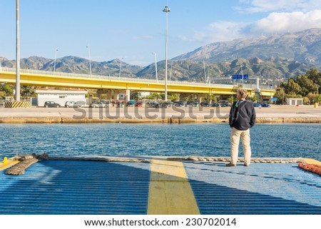 Person standing on a lowered ramp of a sailing ferry - stock photo