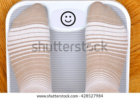 Person standing on the weight scale. The scale shows smiley face - stock photo