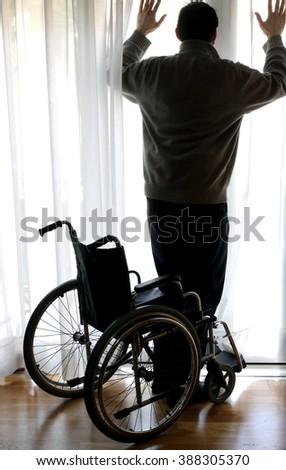 person standing with the wheelchair by the window