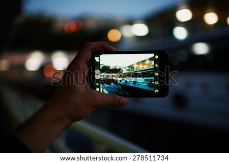 Person taking a photo of touristic sail boat using smart phone camera,male hand holding cell phone while taking a photograph of night lights city in travel,taking a picture of outdoors,blur background - stock photo