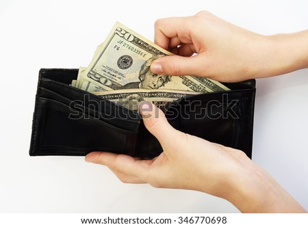 Person taking twenty dollars money from black wallet