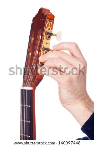 Person tuning a guitar from its headstock - stock photo