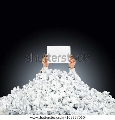 Person under crumpled pile of papers with hand holding a help sign - stock photo