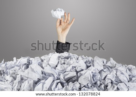 Person under pile of documents with hand holding a crumpled paper - stock photo