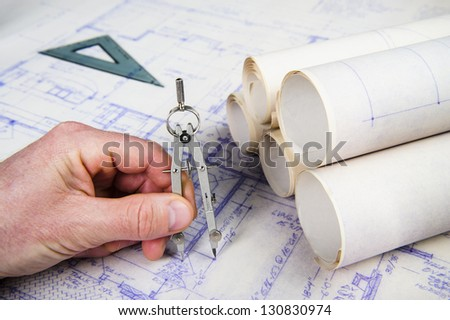 person using a compass to make measurements on a blueprint - stock photo