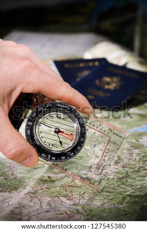 person using a compass to navigate with a map - stock photo
