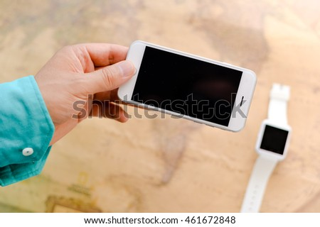 Person using mobile phone above the smart watch background, closeup top view, flat lay mockup style