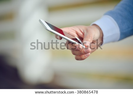 Person using mobile smartphone on white fence planks background. close up photo