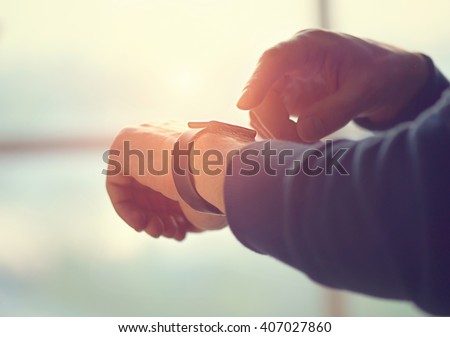 Person using smart watch. Young man making gestures on a wearable smart watch computer device, smartwatch close up (unrecognizable) - stock photo