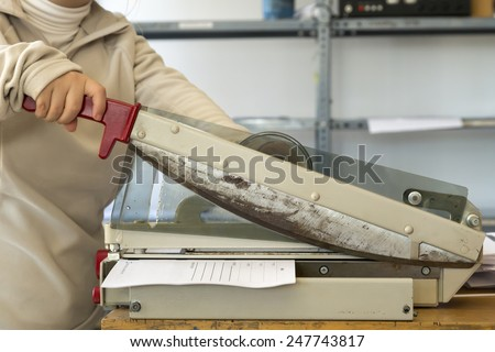 person using the guillotine cutting printing paper