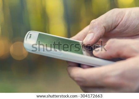 Person using their white smartphone in the forest at sunset close up