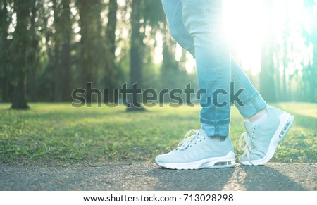 Person walking in nice gray comfortable running shoes in the green park in sunlight, closeup