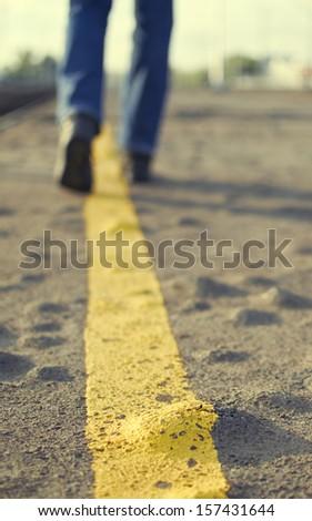 Person walking on asphalt road. - stock photo