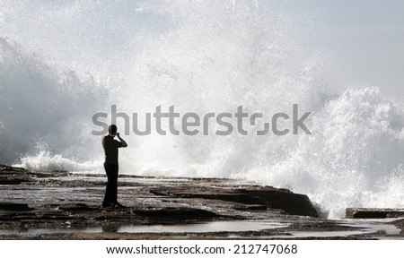 Person watching a huge powerful wave crashing against the rocks - stock photo