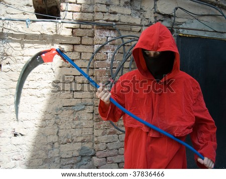 Person wearing black mask and red hood holding scythe