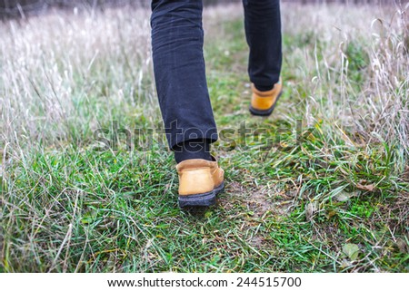 Person wearing walking shoes takes a step on a mountain hiking path, closeup photo. - stock photo