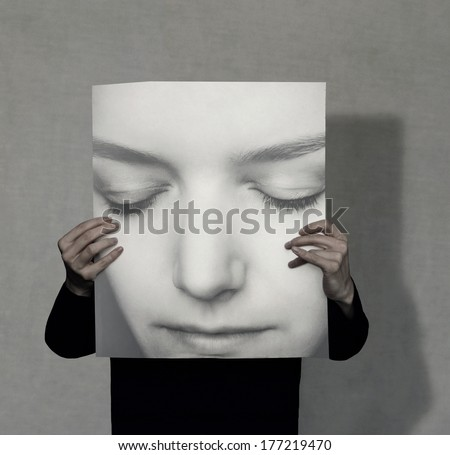 Person who holds a large female portrait on grey background - stock photo