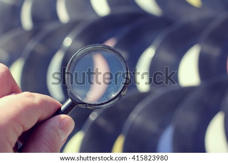 person with a magnifying glass looking for your favorite song in the old records/search for songs and music