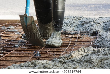 person with gum boots spreading ready mix concrete - stock photo