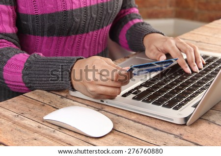 Person with laptop using a credit for online banking and shopping - concept for e-commerce and online banking - stock photo