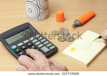 person with money at a desk using a calculator and pen