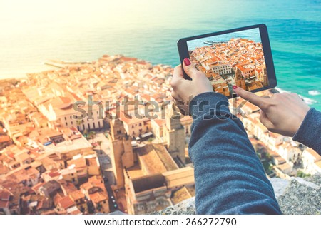 Person with tablet makes pictures of old city from the hill. Toned image - stock photo