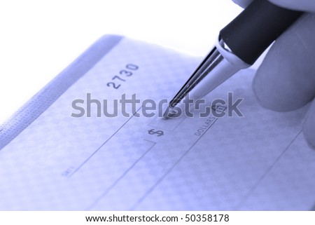 Person writing check with pen and checkbook - stock photo