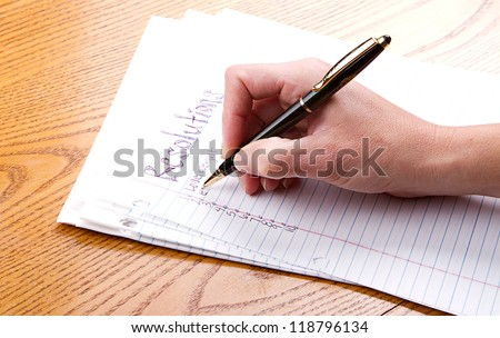 Person writing resolutions on paper