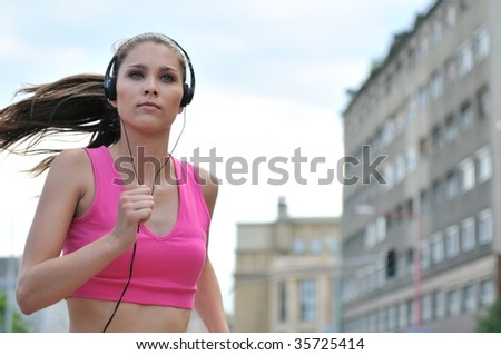 Person (young beautiful woman) listening music running (jogging) in city street - stock photo