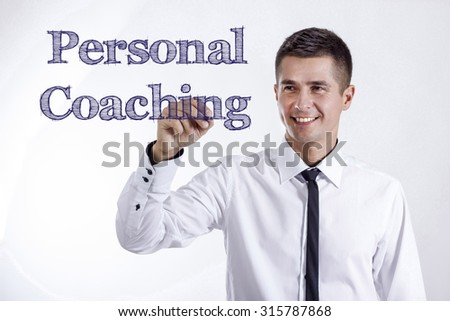 Personal Coaching - Young smiling businessman writing on transparent surface - stock photo