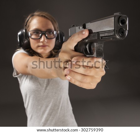 PERSONAL DEFENSE, GUN SAFETY | Young woman learning proper gun control and weapon safety, wearing safety glasses and ear protection.  Her finger is straight and off the trigger on dark background. - stock photo