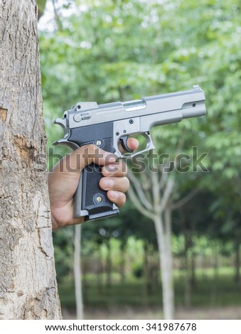 PERSONAL DEFENSE.Man pointing a gun at the target on nature background, selective focus - stock photo