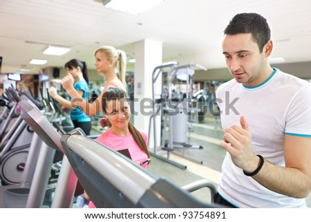 personal female trainer instructing man on treadmill at gym