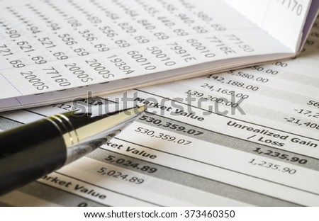 Personal Finance and Investment Planning concept. Pen and Bank Account on investment statement report.