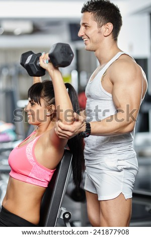 Personal fitness instructor helping a young woman doing workout with dumbbells