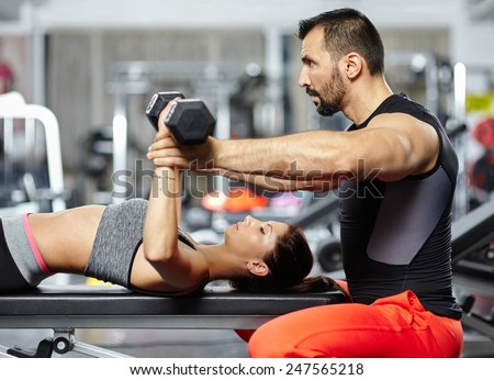 Personal fitness instructor helping a young woman with her chest workout