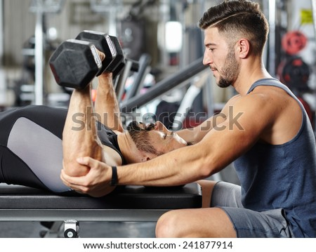 Personal fitness trainer helping a man at a chest workout with heavy dumbbells - stock photo
