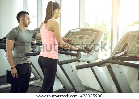 Personal fitness trainer watching his private client while walking on treadmill in modern fitness studio facility. - stock photo
