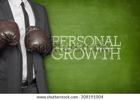 Personal growth on blackboard with businessman wearing boxing gloves - stock photo
