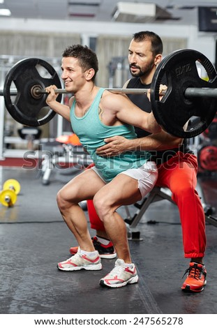 Personal instructor helping an athlete with his barbell squats - stock photo