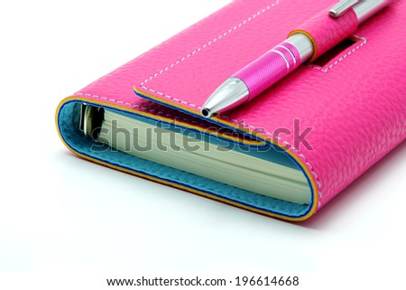Personal Organizer in Pink Color with Ballpoint Pen on White Background - stock photo