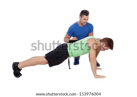 Personal trainer and boy making push-ups isolated on a white background - stock photo