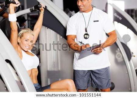 personal trainer and customer in gym - stock photo
