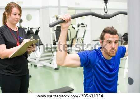 personal trainer and man in gym - stock photo