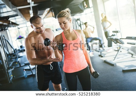 Personal trainer and student in gym working hard