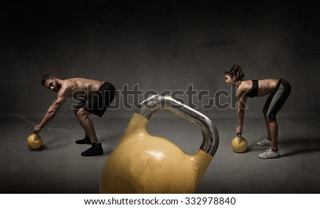 personal trainer and student with kettleball, dark background - stock photo