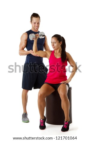 Personal trainer assists beautiful woman lifting dumbbell