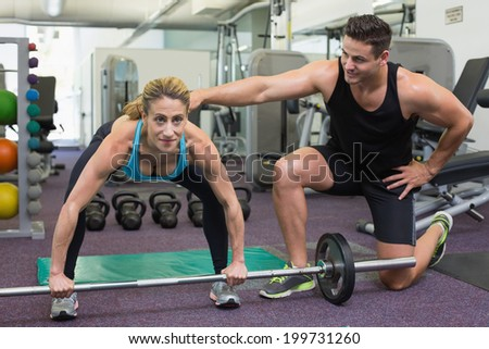 Personal trainer coaching female bodybuilder lifting barbell at the gym - stock photo